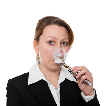businesswoman smokes an electric cigarette in front of white photo