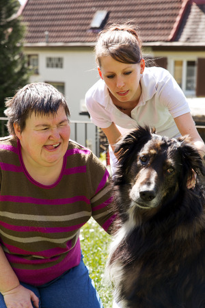 syndrome: disabled woman is making a animal-assisted therapy