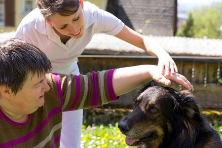 personas discapacitadas: La terapia asistida por animales con un perro mestizo Foto de archivo