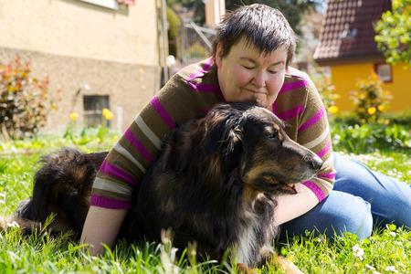 verstandelijk gehandicapte vrouw ligt met hond op een grasveld Stockfoto