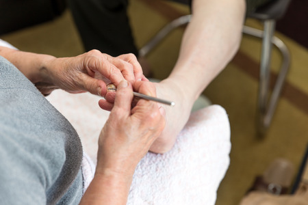 chiropodist: a chiropodist at home makes a treatment of the feet Stock Photo