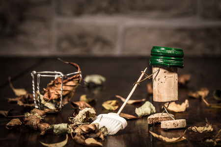 tidying up: Concept sweep leaves with a broom, wine cork figures Stock Photo
