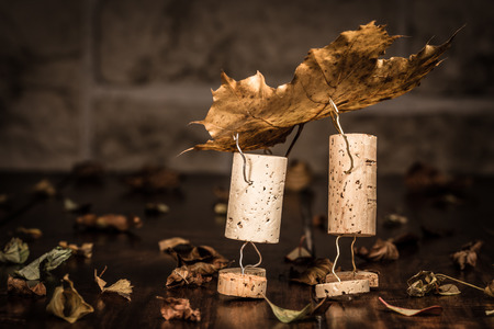 humanly: Concept two men carry leaves, wine cork figures