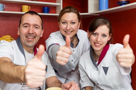 Punkty personelu pielęgniarskiego do widza i podnosząc kciuki Zdjęcie Seryjne