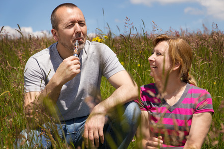 couple in a meadow with electric cigarette photo