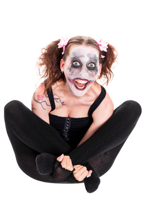 insane female clown in front of white looks to the viewer photo