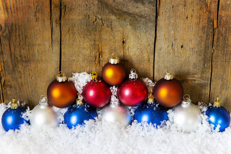 wooden background with colorful christmas balls with snow photo