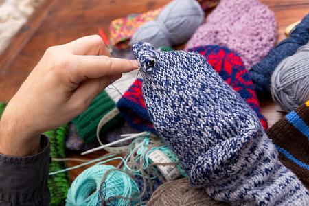 darn: closeup of male hands darn wool socks