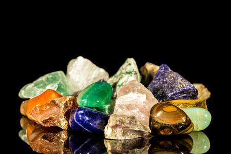 various gemstones, uncut and Tumble finishing with black background and reflection