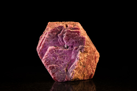 ruby stone: rough ruby mineral stone in front of Black