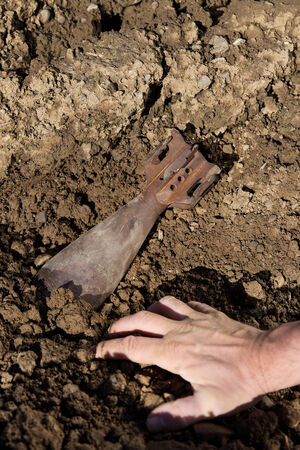 defuse: close up from a hand and a old grenade in the soil