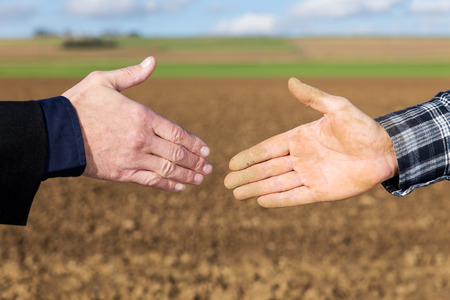 Close up Handshake between businessman and farmer Imagens