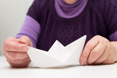 female senior adult: female senior adult with a paper boat Stock Photo