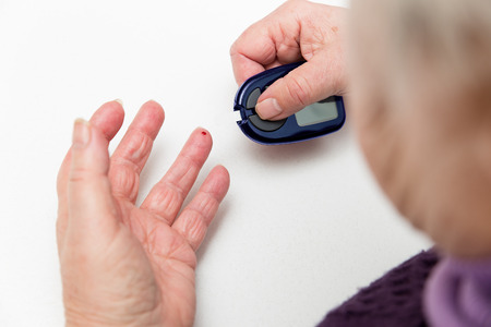 bleed: some female senior adult hands with glucometer