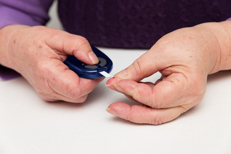 bleed: glucometer and bleed on a finger of a senior adult