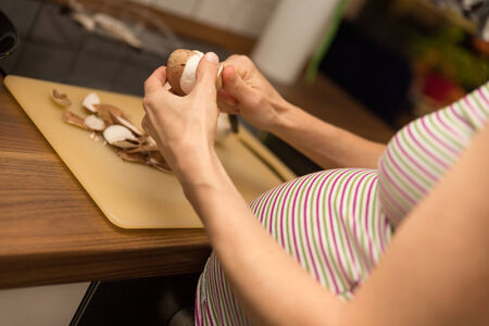 adequate: a pregnant woman is cutting mushrooms in the kitchen