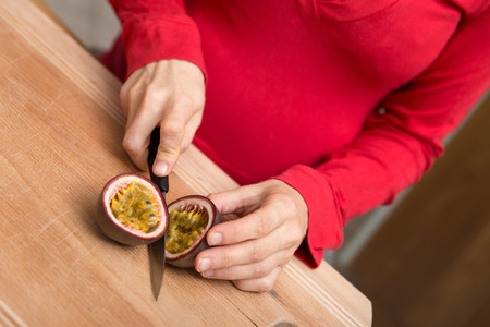 adequate: closeup for a pregnant woman is cutting a passion fruit