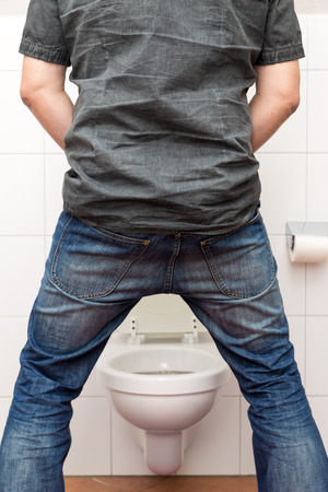 urinate: a man peeing standing up in the restroom