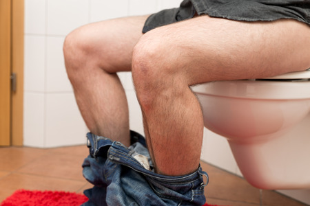 closeup man sitting on a toilet bowl in the restroom photo