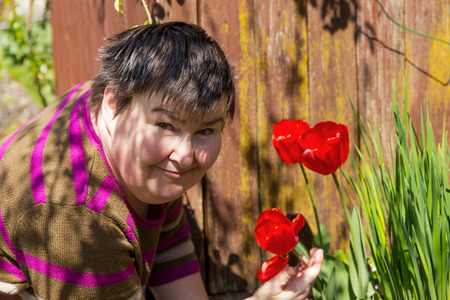 mentally disabled woman smells on a flower