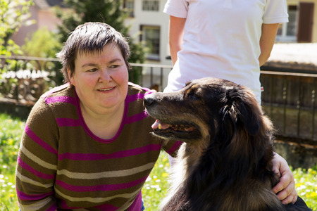 dog health: mentally disabled woman is caress a dog