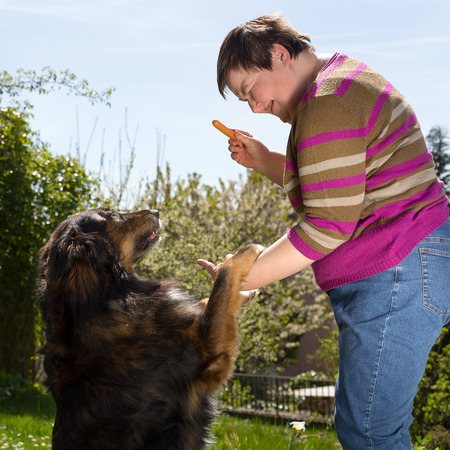 medical attendance: mentally disabled woman is feeding a dog Stock Photo
