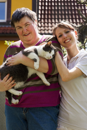 care giver: disabled woman is holding a cat female caregiver in the background