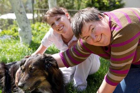 dog health: two women and a half breed dog on a field