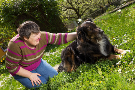 home health care: disabled woman on a lawn is stroking a dog Stock Photo