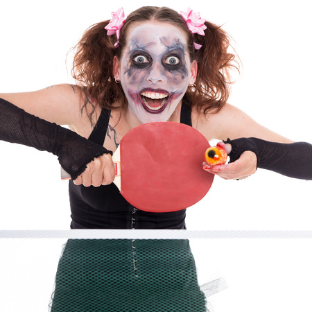 psychopath: scary female clown is playing ping-pong with an eye
