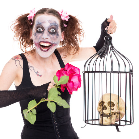 roses and blood: insane girl with rose and skull in a birdcage Stock Photo
