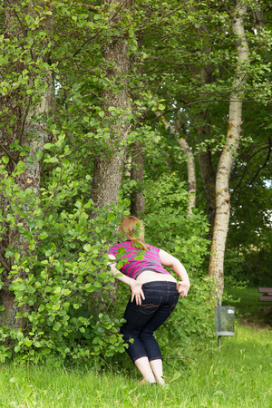 woman is peeing outdoors behind bushes