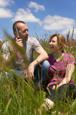 adult couple with e-cigarette in a meadow photo