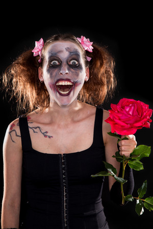 insane funny female clown with red rose in front of black photo
