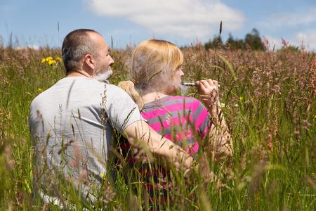a couple enjoys an e-cigarette in the nature