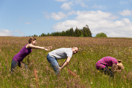3 persons only: a group of people are leapfrogging for fun Stock Photo
