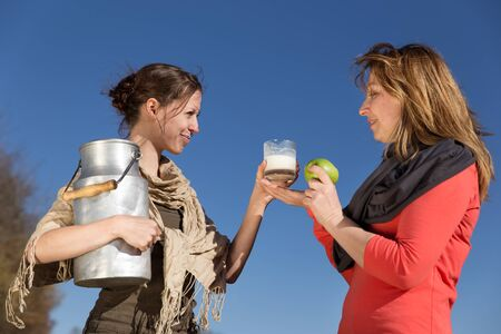 milk jug: Two women with healthy food are smiling to eachother