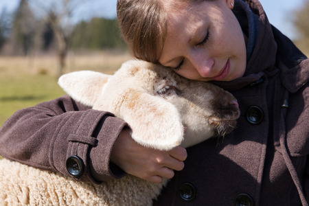 pretty woman is intimately hugging a little lamb