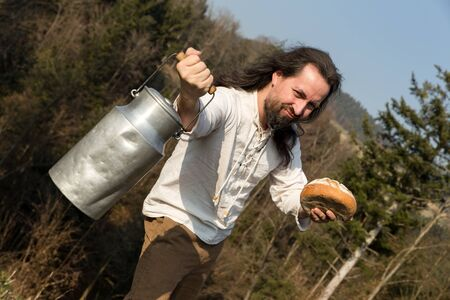 long haired: a long-haired grower offering a milk churn and bread