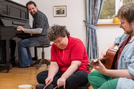 terapia de grupo: una terapia de música con una mujer con discapacidad mental, Foto de archivo