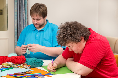 crafts person: a mentally disabled woman and young man doing arts and crafts Stock Photo
