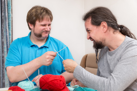 knitting needles: two young men are fighting with knitting needles