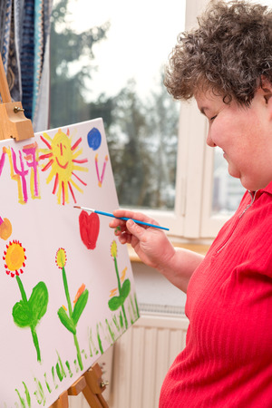 mentally: a mentally disabled woman painting a picture