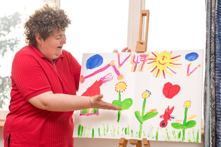 terapia psicologica: una mujer con discapacidad mental que muestra su pintura Foto de archivo