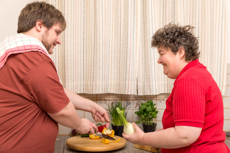 a handicapped woman and a young man in the kitchen Stock Photo