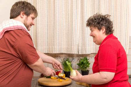 obeso: una mujer con discapacidad y un hombre joven en la cocina