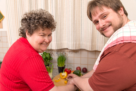 personas discapacitadas: una mujer con discapacidad mental y un joven cocina juntos