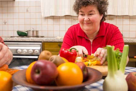 a mentally disabled woman learns cooking in the kitchen