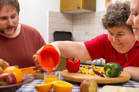 personas discapacitadas: una mujer con discapacidad mental y dos cuidadores que cocinan junto