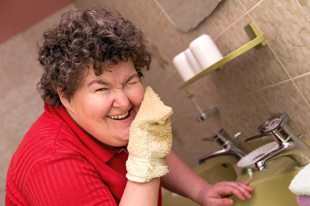 a happy mentally disabled woman with a washcloth
